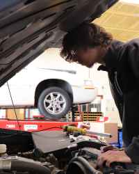 Auto Service Student Working on Engine